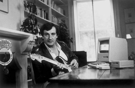 Douglas Adams with Mac 128k and electric guitar