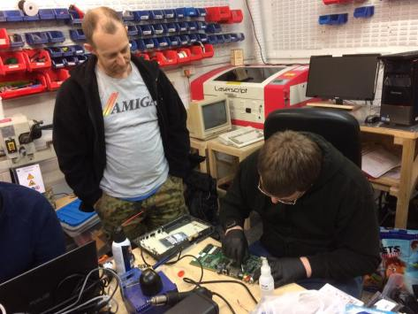 A CD32 motherboard being re-capped, with Zeb Elwood (standing) and Scott MacDonald. [Pic Robert Hazelby]