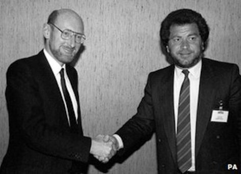 Sir Clive Sinclair shakes hands with Alan Sugar at the sale of Sinclair to Amstrad, 1986 (PA)